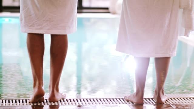 couple in bathrobes next to the pool - località turistica video stock e b–roll