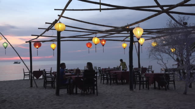 A couple in beach restaurant at sunset