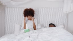 Couple In Bed With Woman Ill And Suffering With Symptoms Of Cold