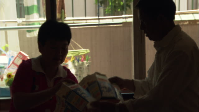ms couple in bedroom sewing together used milk cartons, shanghai, china - coppia di età matura video stock e b–roll