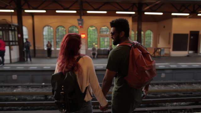 couple in berlin waiting for train laughing and holding hands - vänta bildbanksvideor och videomaterial från bakom kulisserna