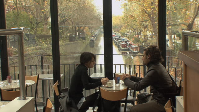 MS Couple in café straddling the Regent canal in Little Venice / London, UK.