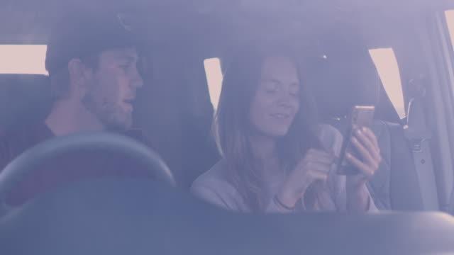 couple in camper van on road trip looking at smart phone - passenger seat stock videos & royalty-free footage