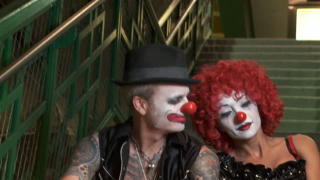 CU, Couple in clown costumes sitting on steps, Los Angeles, California, USA, TU
