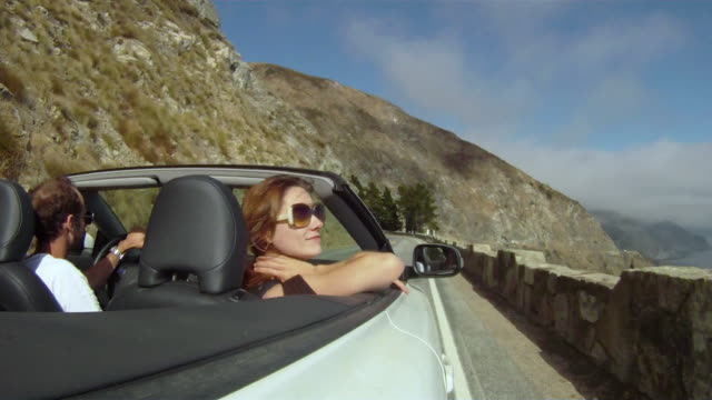 ws pov couple in convertible car driving on country road / big sur, california, usa - cabrio stock-videos und b-roll-filmmaterial