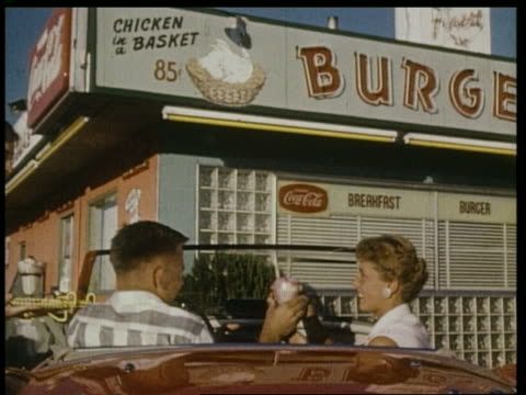 1959 rear view couple in convertible having milk shakes in drive thru - 1950 1959 個影片檔及 b 捲影像