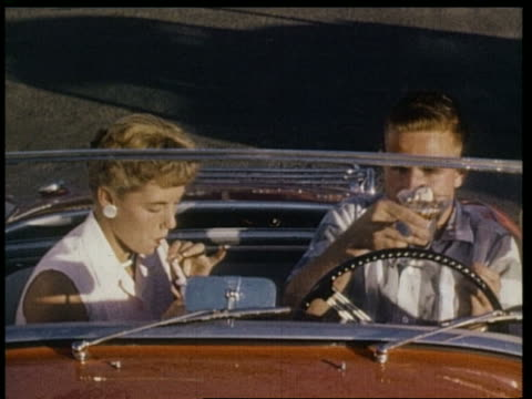 1959 couple in convertible having milk shakes in drive thru