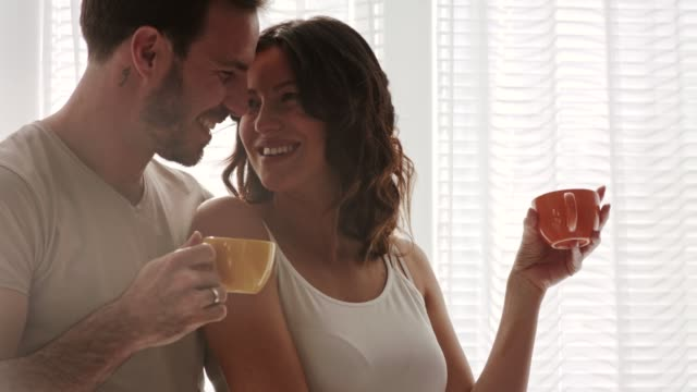 couple in embrace enjoying their morning coffee and having a moment of bonding - mid adult couple stock videos & royalty-free footage