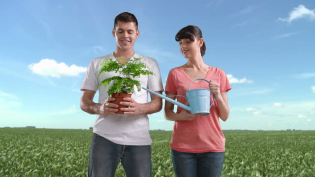 Couple in field holding plant and watering can