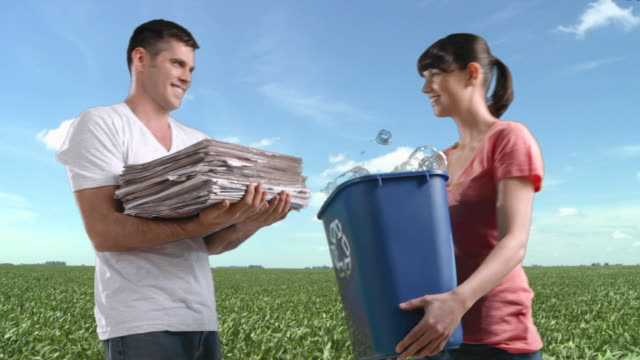 couple in field holding recycling bin and pile of newspapers - societal symbol stock videos & royalty-free footage