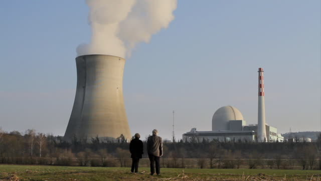 WS Couple in foregrand looks onward towards nuclear reactor / Schonau, Germany