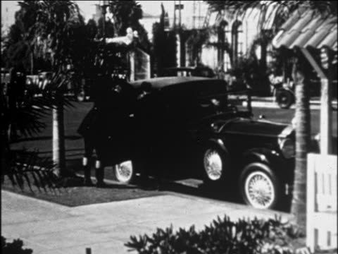 B/W 1929 couple in formalwear exiting limousine as chauffeur stands by / Ambassador Hotel, Hollywood