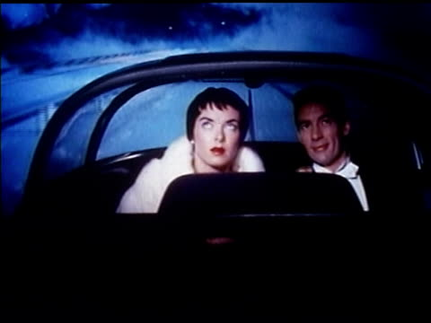 vidéos et rushes de 1956 couple in formalwear ride in futuristic car on foggy futuristic highway at night - 1956