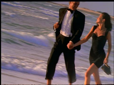 couple in formalwear running on beach - paar mittleren alters stock-videos und b-roll-filmmaterial