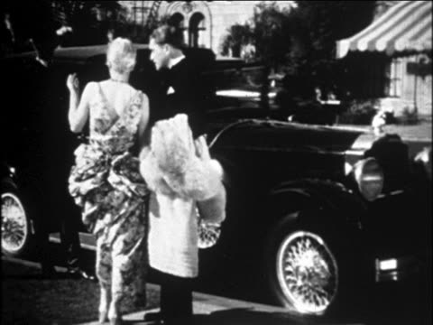 b/w 1929 couple in formalwear standing by limousine / chauffeur in background / ambassador hotel, hollywood - 1920 1929 stock videos & royalty-free footage