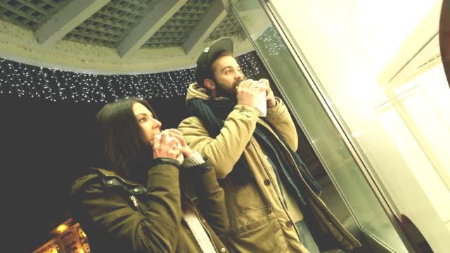 vídeos de stock e filmes b-roll de couple in front of shop window eating burgers - ver montras