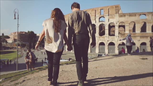 Couple in front of the Coliseum, hand in hand