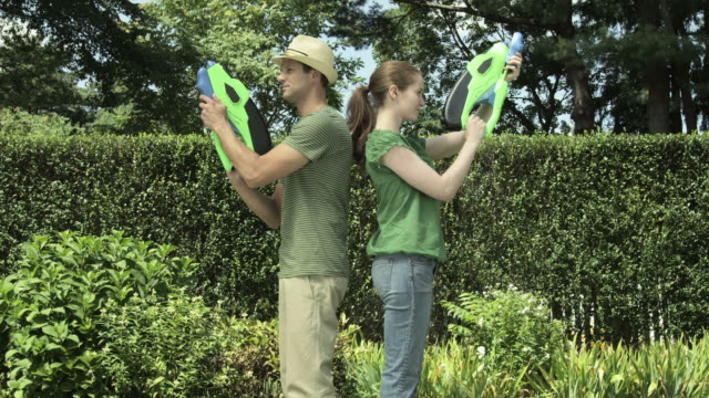 couple in garden with water pistols - squirting woman stock videos and b-roll footage