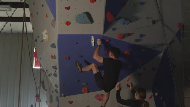 couple in gym working out on rock climbing wall - arrampicata libera video stock e b–roll