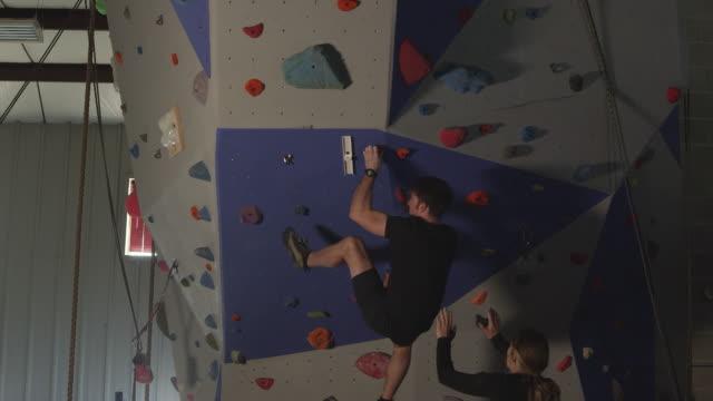 couple in gym working out on rock climbing wall - friklättring bildbanksvideor och videomaterial från bakom kulisserna