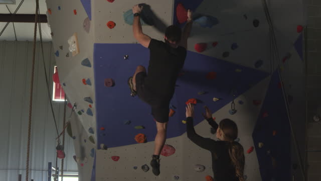 couple in gym working out on rock climbing wall while he climbs - arrampicata libera video stock e b–roll