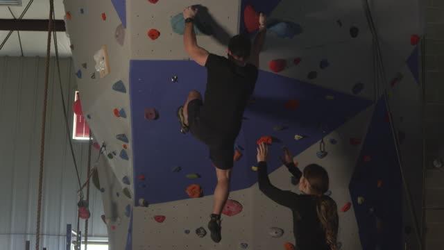 couple in gym working out on rock climbing wall while he climbs - friklättring bildbanksvideor och videomaterial från bakom kulisserna