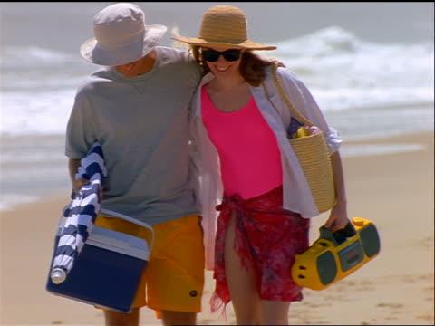 couple in hats + sunglasses carrying beach gear + walking on beach toward camera - サングラス点の映像素材/bロール