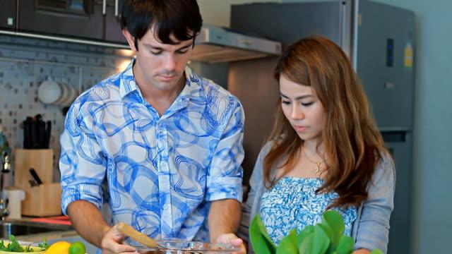 vídeos y material grabado en eventos de stock de par en la cocina juntos preparar comida - pareja de mediana edad