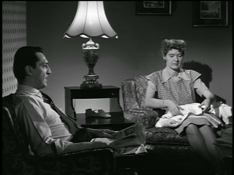 b/w 1954 couple in living room talking / man with newspaper as woman sews / industrial - 1954 stock videos and b-roll footage