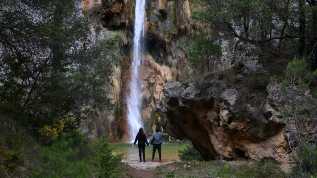 couple in love discovering beautiful tall waterfall in a wild and tranquil place in the catalan pyrenees. - area selvatica video stock e b–roll