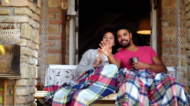 couple in love enjoying on porch swing - altalena video stock e b–roll