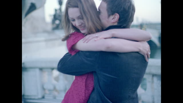 vídeos de stock e filmes b-roll de couple in love hugging and twirling by the seine river in paris - gola alta
