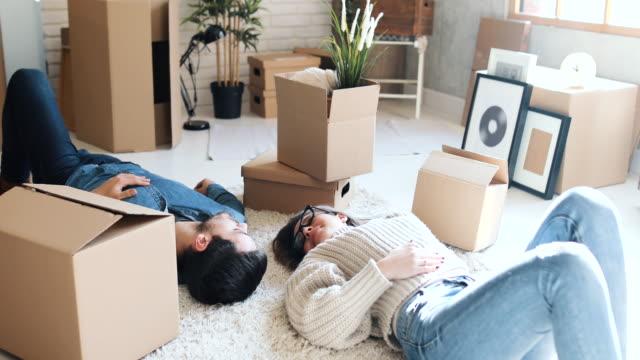 vidéos et rushes de un couple dans l'amour couché sur le tapis dans leur nouvelle maison. il y a des boîtes autour d'eux. ils sont heureux - appartement
