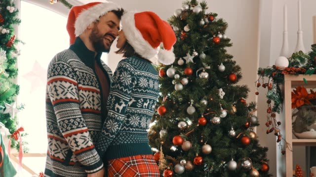 Couple in love rubbing their noses together in front of a Christmas tree
