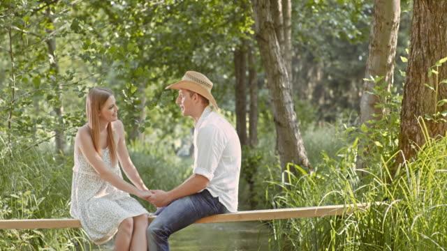SLO MO TD Couple in love sitting on a footbridge