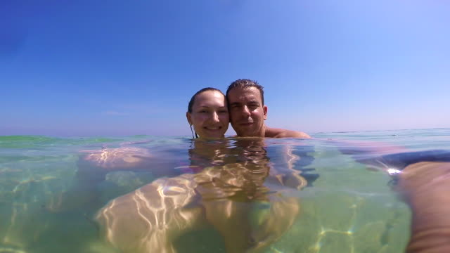 couple in love swimming in the paradise waters of indonesia recording himself doing video selfie during travel vacations. - zungenkuss stock-videos und b-roll-filmmaterial