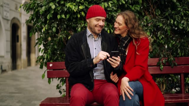 couple in love using smart phone - panchina video stock e b–roll
