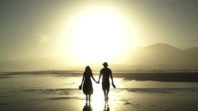 couple in love walking on a hot day on the beach at sunset - weekend activities stock videos & royalty-free footage