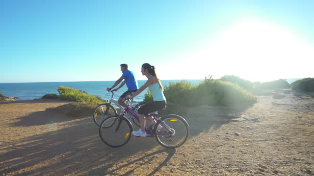 couple in mountain bike near to the sea - mountain biking stock videos & royalty-free footage