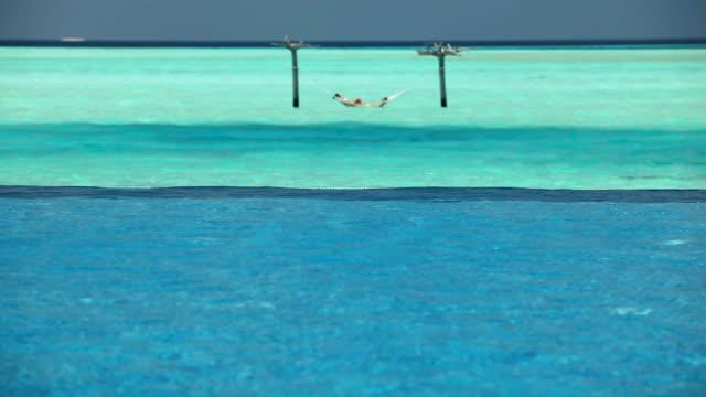 couple in ocean hammock beyond swimming pool, maldives, indian ocean - pool mit gegenströmung stock-videos und b-roll-filmmaterial