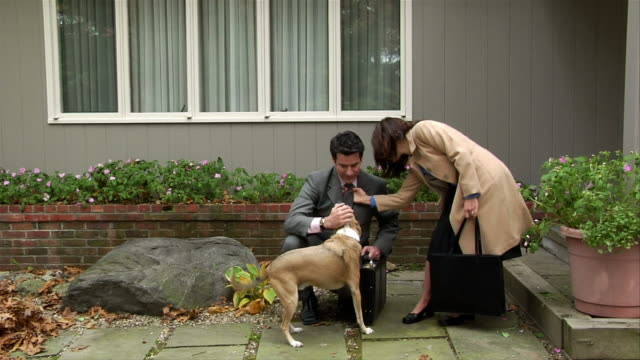 Couple in professional clothing petting dog in front of house / dog running left