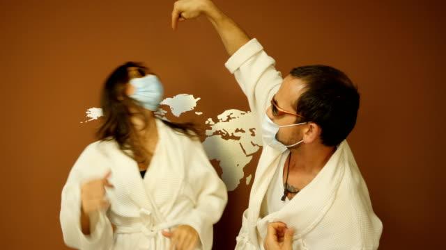 vídeos de stock, filmes e b-roll de casal em quarentena em casa usando uma máscara, mas tentando se divertir - perigo