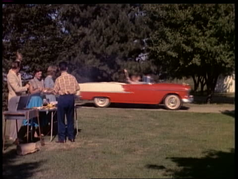 stockvideo's en b-roll-footage met 1955 couple in red + white convertible chevrolet stop in driveway + wave to people barbecuing - 1955
