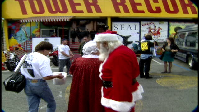 couple in santa and mrs clause outfits walking into tower records in los angeles california - weihnachtsfrau stock-videos und b-roll-filmmaterial