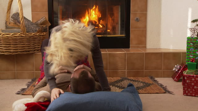 couple in santa claus hats kisses in front of the fireplace / bellevue, idaho, united states - davanti video stock e b–roll