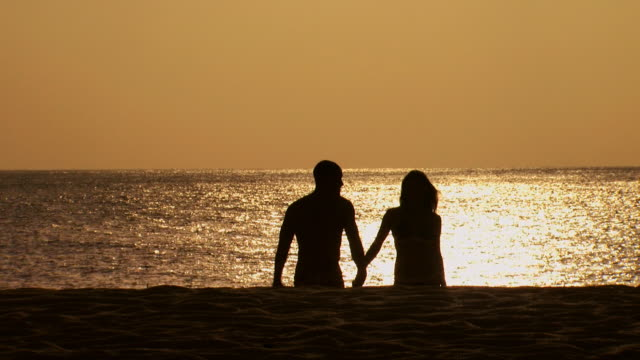 couple in silhouette holding hands on beach at dusk - see other clips from this shoot 1142 stock videos & royalty-free footage