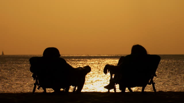 couple in silhouette sitting in folding chairs on beach at dusk holding hands - この撮影のクリップをもっと見る 1142点の映像素材/bロール