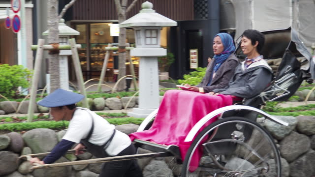 couple in southeast asia sights japan by rickshaw. - jinrikisha stock-videos und b-roll-filmmaterial