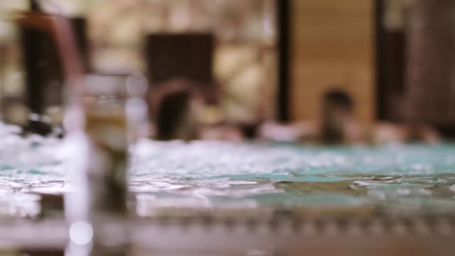 couple in spa pool, glass of water in foreground - mid adult couple stock videos & royalty-free footage