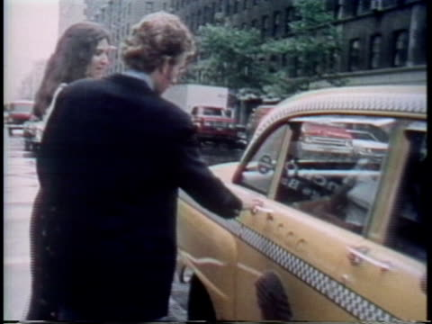 1975 ms couple in street getting into checkered cab/ new york city - 1975 stock videos & royalty-free footage